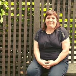 Jo-Anne Gauthier, a white woman with bangs and shoulder-length red hair sits in a garden, in front of a wood lattice fence. She is smiling, her hands together, wearing a black shirt and dark pants.