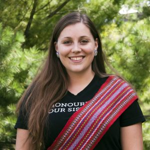 """Brittany, an Indigenous woman with long brown hair, stands in front of tree branches. She is smiling, and wearing a black shirt with text """"Honour Our Sisters"""" under a red Michif sash."""