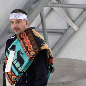 An Kwantlen Indigenous man, with short dark hair and a grey bread. He's wearing a white patterned bandana, and a sash patterned with caribou over a dark jacket.