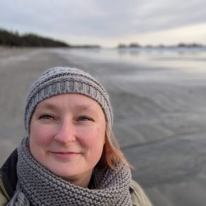 headshot of a white woman standing on a grey beach. She's wearing a grey toque and scarf, and has blonde shoulder-length hair under her toque. She's smiling, looking to the sky.