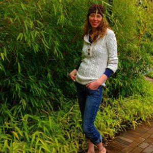 Full body image of a white woman standing among tall bamboo, with long light brown hair and a headband. She is smiling and wearing jeans, a white sweater, and a blue undershirt.