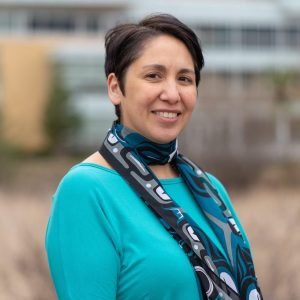 Headshot of a Nlakap'mux and Sto:Lo Indigenous woman with short brown hair parted on the side. Smiling, wearing a turquoise long sleeve shirt and a scarf of black, white, grey, and blue.